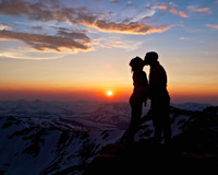 Couple Kissing On Mountain Sunset